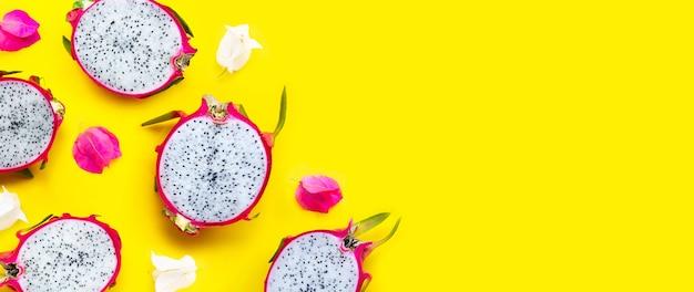 Fruta do dragão ou pitaya com flores de buganvílias em fundo amarelo.
