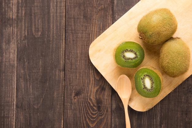 Fruta e colher frescas de quivis na placa de madeira.