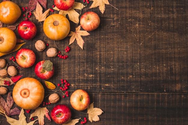 Fruta e folhas do outono no fundo de madeira
