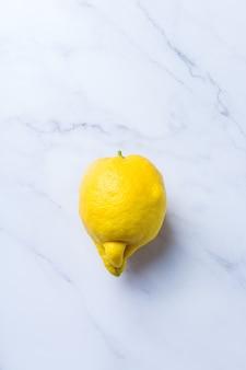 Fruta feia da moda, limão amarelo suculento engraçado com forma imperfeita em uma mesa de mármore branco. os agricultores produzem, orgânico, conceito estranho de desperdício de alimentos deformados. vista superior, copie o fundo do espaço