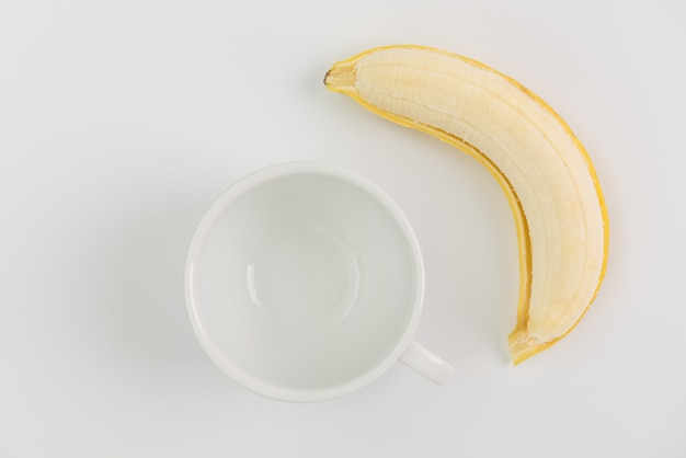 Fruta fresca da banana da casca e copo de café branco no fundo branco