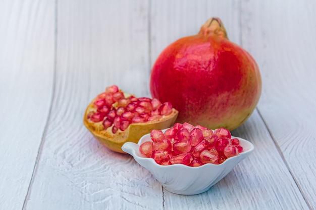 Fruta fresca da romã no branco de madeira.