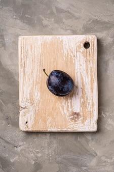 Fruta fresca de ameixa madura na tábua de madeira, fundo de pedra de concreto, vista superior