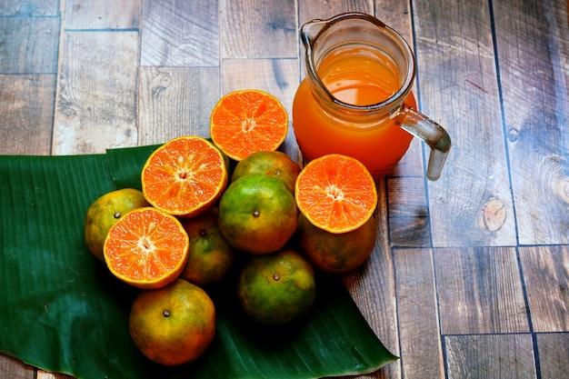Fruta fresca de laranja e suco de laranja em uma mesa de madeira
