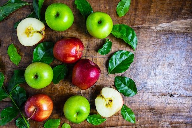 Fruta fresca, maçã verde e maçã vermelha em um fundo de madeira