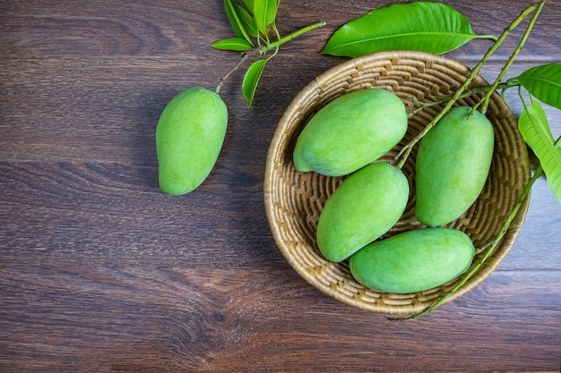 Fruta fresca manga verde em uma cesta de madeira