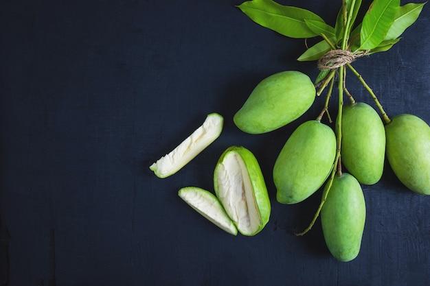 Fruta fresca manga verde em uma mesa de madeira
