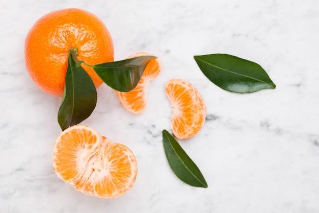 Fruta fresca tangerina tangerina crua com folhas em fundo de mármore
