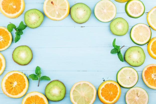 Fruta. frutas frescas coloridas na placa de madeira azul. laranja, kiwi, limão, camada plana, vista superior,