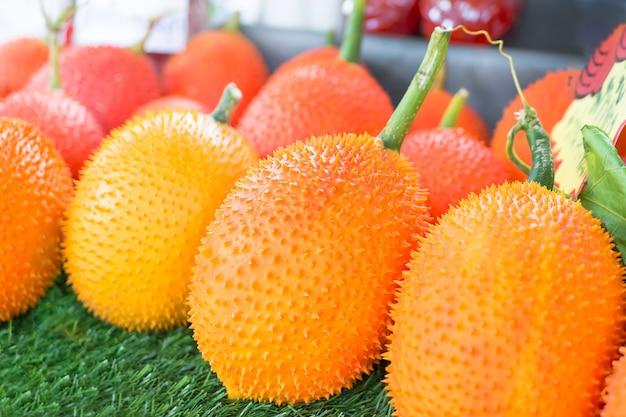 Fruta gac, baby jackfruit, spiny bitter gourd em caixa de madeira.