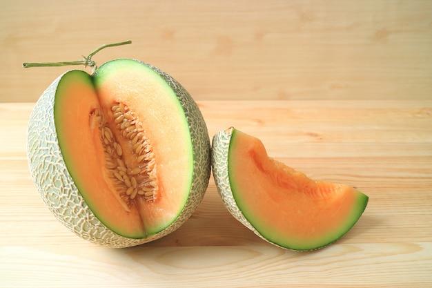 Fruta inteira de melão maduro fresco com um pedaço de fruta em fatias sobre uma mesa de madeira