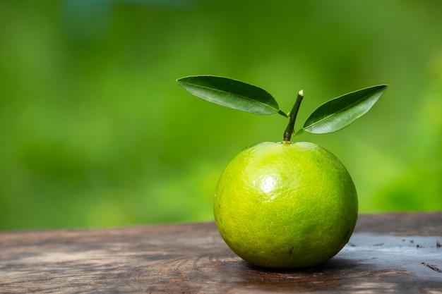Fruta laranja colocada sobre um piso de madeira e com um verde natural.