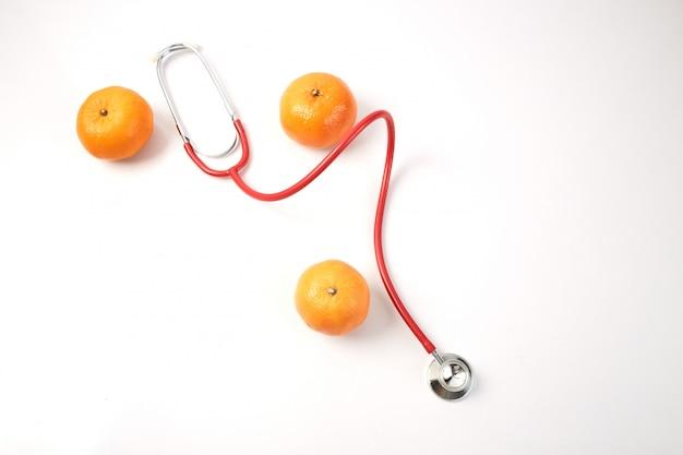Fruta laranja com estetoscópio vermelho sobre branco