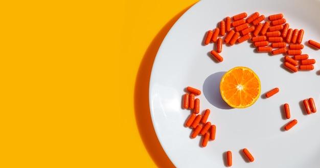 Fruta laranja com pílulas cápsulas em chapa branca em fundo laranja.