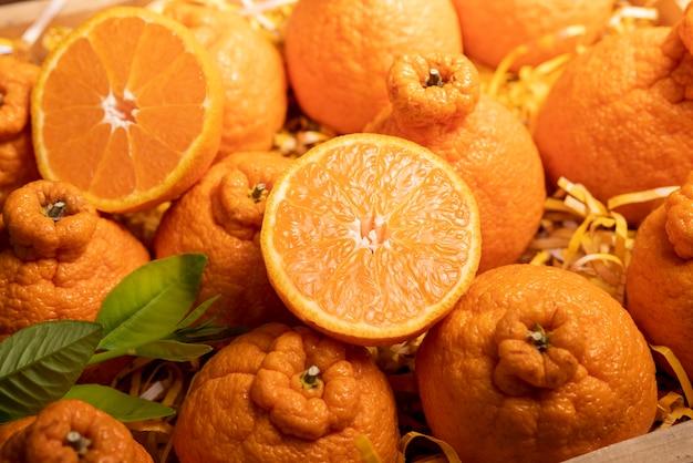 Fruta laranja com rodelas e folhas de laranja em caixinha de madeira, laranja dekopon ou tangerina sumo com folhas em embalagem caixa.