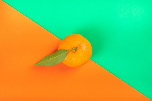 Fruta laranja na superfície laranja e verde colorida