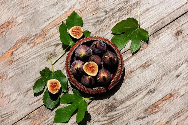 Fruta madura de figo roxo com folhas em uma tigela de madeira com fundo de madeira
