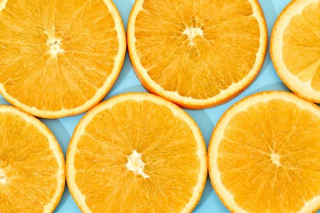 Fruta madura de laranja fatia sobre fundo azul. vista do topo