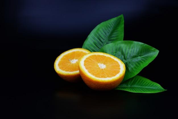 Fruta madura meio laranja útil com folha sobre um fundo preto isolado