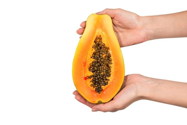 Fruta mamão isolada em um fundo branco nas mãos da mulher. fruta tropical. meio mamão.
