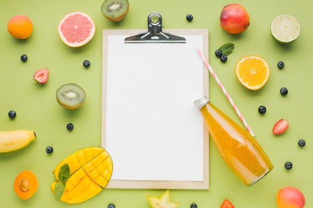 Fruta saborosa e quadro de suco com prancheta