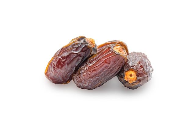 Fruta seca de data medjoul na parede branca isolada com traçado de recorte.