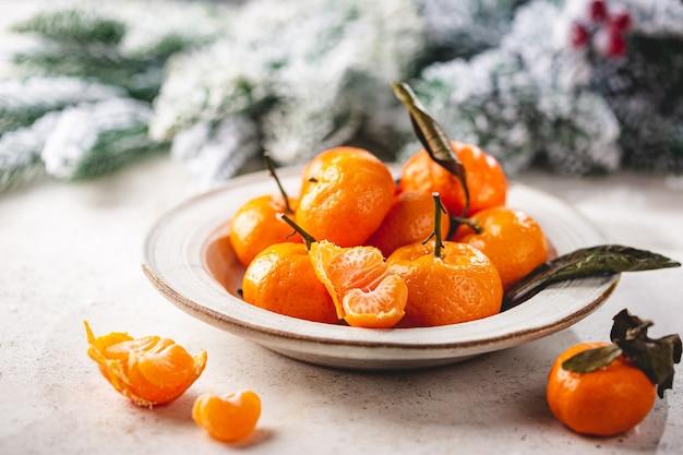 Fruta tangerina fresca ou tangerinas com folhas em uma tigela sobre fundo branco com decorações de inverno