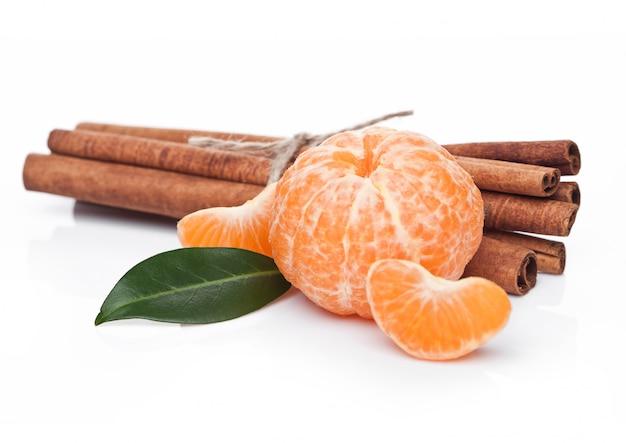 Fruta tangerina orgânica fresca com canela crua no fundo branco