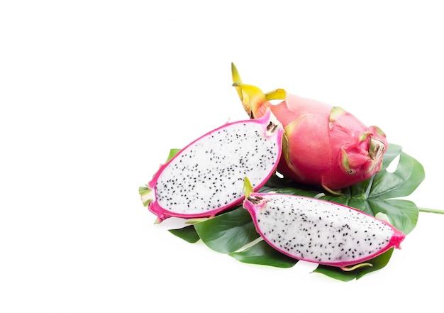 Fruta tropical, fatia saudável do pitaya do dragão nas folhas verdes isoladas,