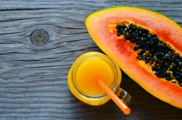 Fruta tropical fresca madura da papaia orgânica com um vidro do suco