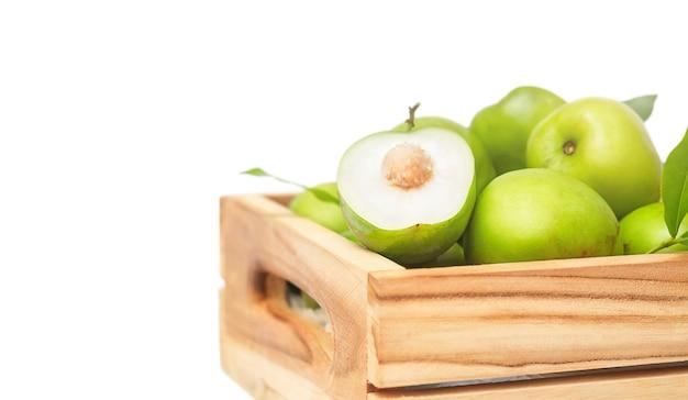 Fruta verde da jojoba e cortada pela metade na caixa de madeira isolada no fundo branco