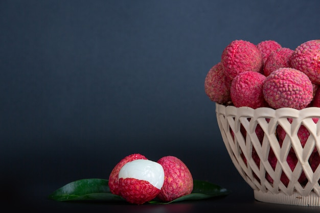 Fruta vermelha do lichi colocada em uma cesta.