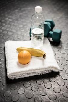 Frutas, água e halteres no ginásio crossfit