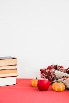 Frutas artificiais e cobertor perto de livros