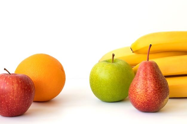 Frutas: banana, laranja, maçã e pêra, isoladas em uma superfície branca. copie o espaço.