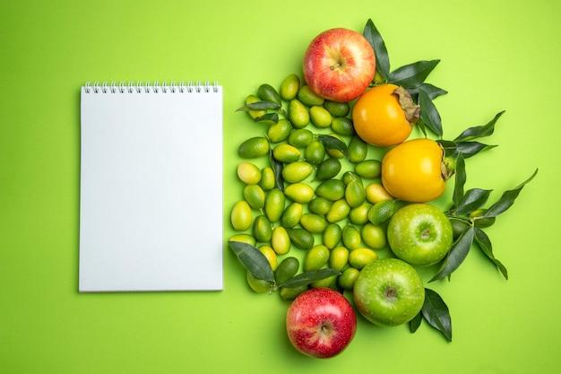Frutas caderno branco caquis maçãs frutas cítricas com folhas