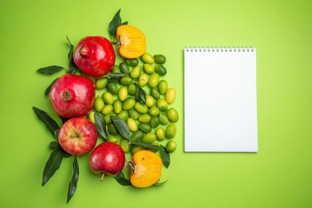 Frutas caderno branco romãs maçãs frutas cítricas caqui