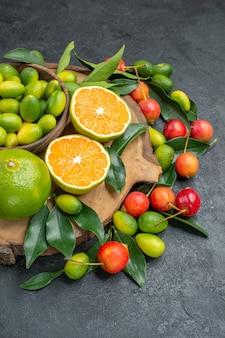 Frutas cerejas frutas cítricas no quadro sobre a mesa escura