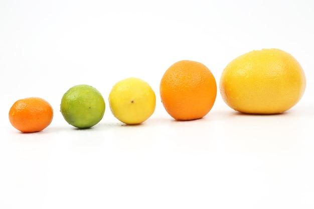 Frutas cítricas caem em uma inclinação sobre um fundo branco