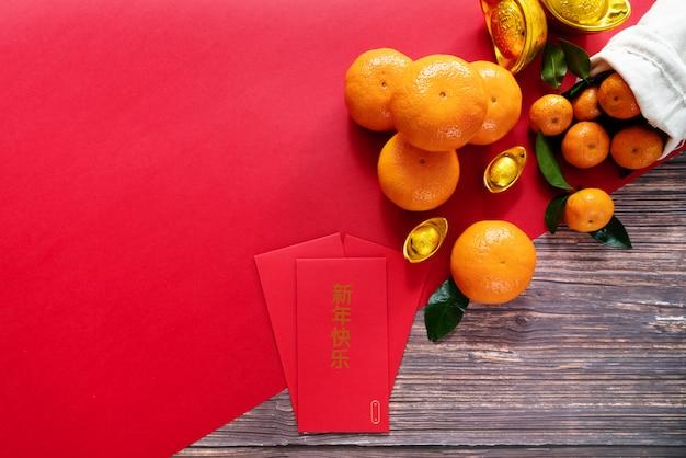 Frutas cítricas caídas no vermelho com envelopes com mensagem chinesa nele