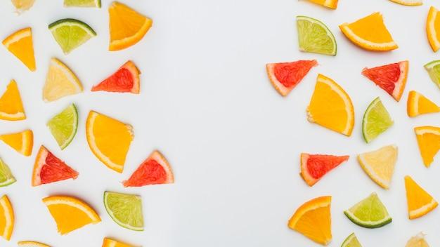 Frutas cítricas coloridas dispostas com espaço entre para escrever texto sobre fundo branco