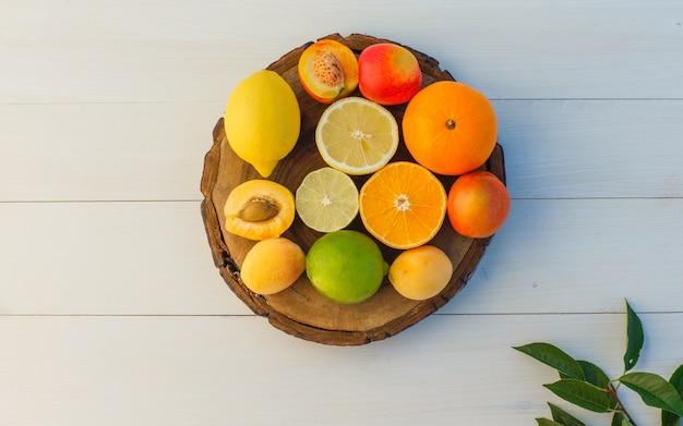 Frutas cítricas com folhas, damascos, nectarinas na tábua e fundo de madeira, postura plana.
