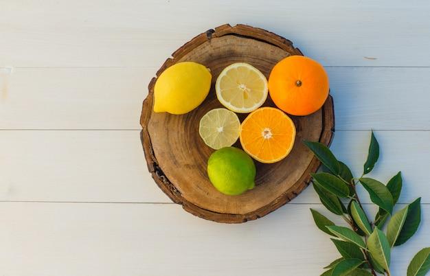Frutas cítricas com folhas na tábua e fundo de madeira, vista superior.
