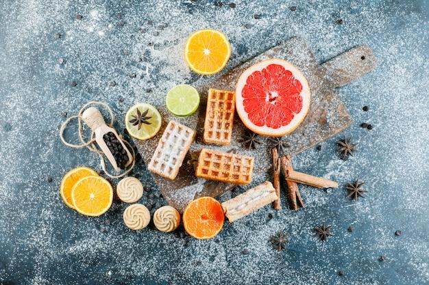 Frutas cítricas com waffle, especiarias, biscoitos, pedaços de chocolate vista superior na placa suja e de corte