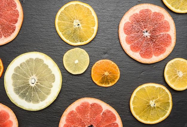 Frutas cítricas cortadas em pedaços redondos: laranja, toranja, limão, tangerina
