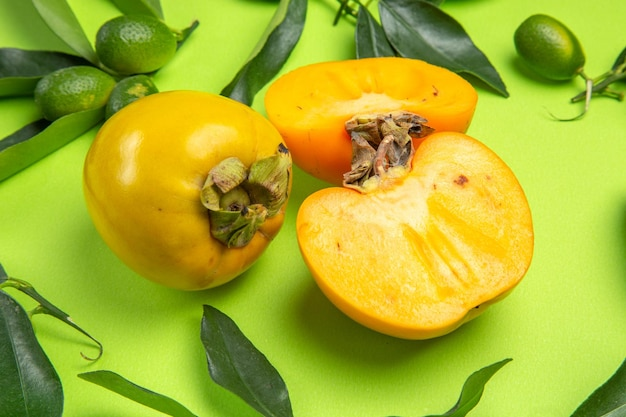 Frutas cítricas de caqui com folhas e três caquis