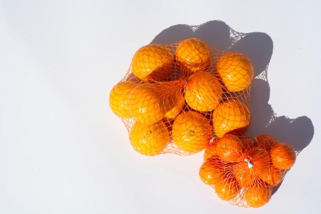 Frutas cítricas de tangerina fresca plana leigos com sombras em um alimento de verão branco, pacote plástico