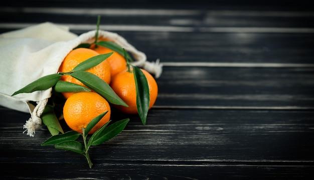 Frutas cítricas de tangerina frescas em saco ecológico em fundo preto de madeira. copie o espaço.
