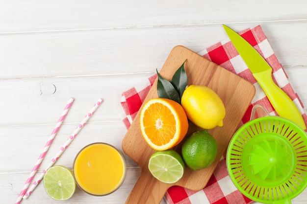 Frutas cítricas e copo de suco. laranjas, limas e limões. sobre fundo de mesa de madeira branca com espaço de cópia