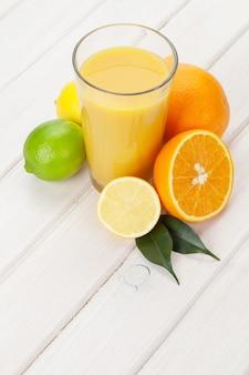 Frutas cítricas e copo de suco. laranjas, limas e limões. sobre fundo de mesa de madeira branca